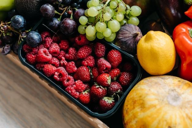 Caixa cheia de várias frutas e bagas orgânicas conceito de entrega de comida