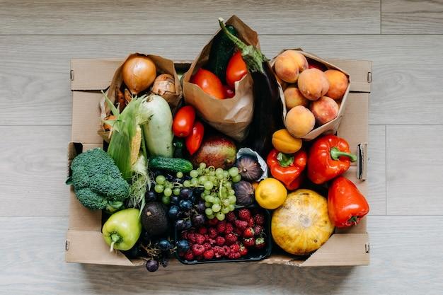 Caixa cheia de vários vegetais orgânicos frescos, frutas e bagas conceito de entrega de comida