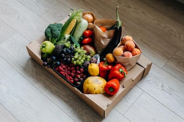 Caixa cheia de vários vegetais orgânicos, frutas e bagas conceito de entrega de comida