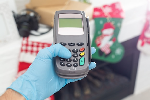 Caixa com a mão segurando a máquina de leitura de cartão de crédito e usando luvas descartáveis, pagando com smartphone durante a pandemia de covid-19.