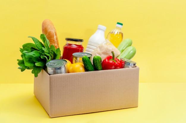 Caixa com alimentos. produtos essenciais: óleo, conservas, cereais, leite, legumes, frutas
