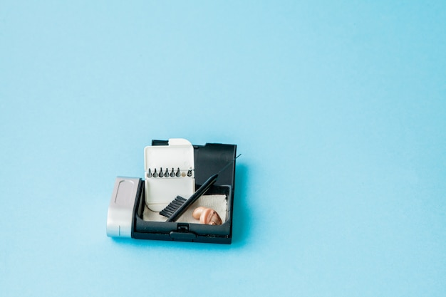 Caixa com aparelho auditivo e acessórios