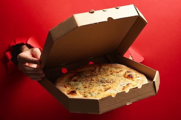 Caixa com as mãos segurando pizza saborosa