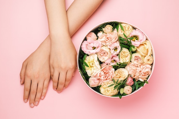 Caixa com belas flores ao lado das mãos da mulher sobre o fundo preto com espaço de cópia. beleza
