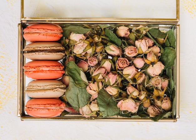 Caixa com botões de flores e biscoitos brilhantes na mesa de luz
