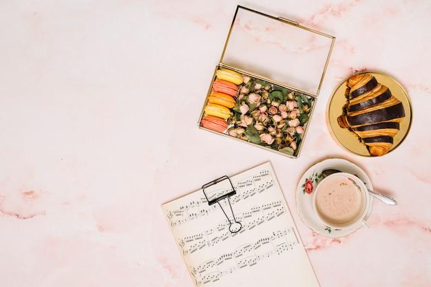 Caixa com botões de flores e biscoitos perto de xícara de café na mesa