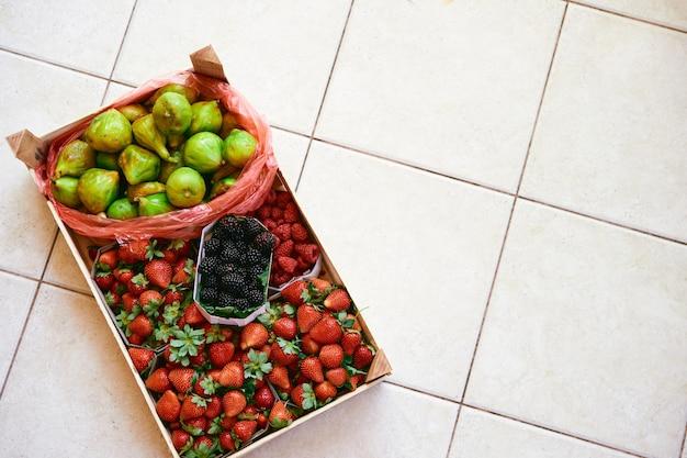 Caixa com caixas de morangos, framboesas, figos e amoras silvestres sobre um ladrilho claro