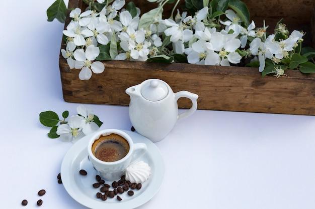 Caixa com galhos de macieira, uma xícara de café, um bule, merengue e grãos de café