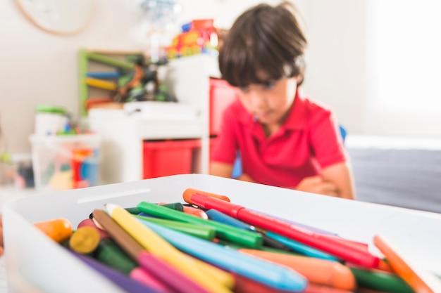 Caixa com lápis de colorir e garoto