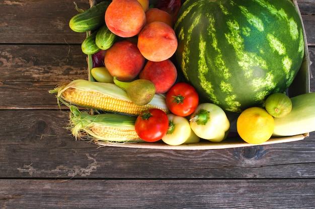 Caixa com legumes e frutas na madeira velha vista superior. postura plana.