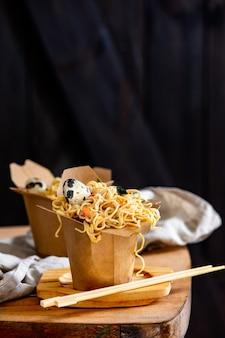 Caixa com macarrão e ovo de codorna em uma tabela