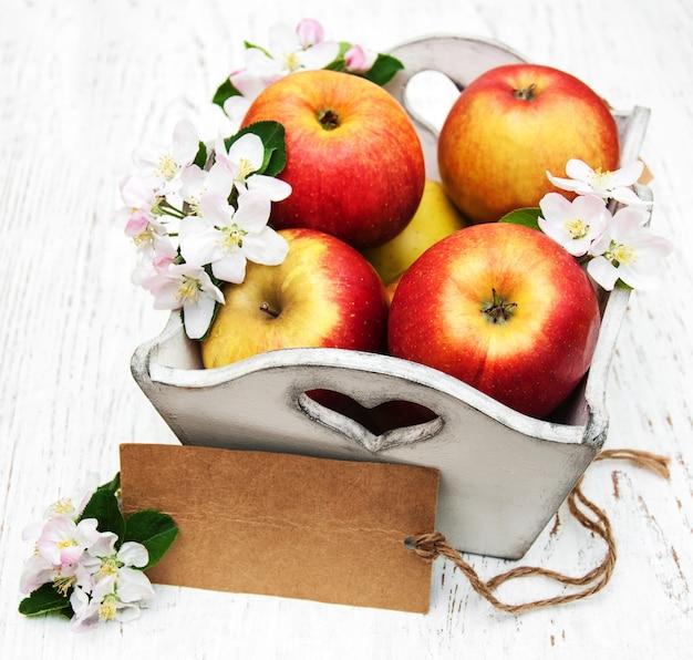 Caixa com maçãs e flores de macieira