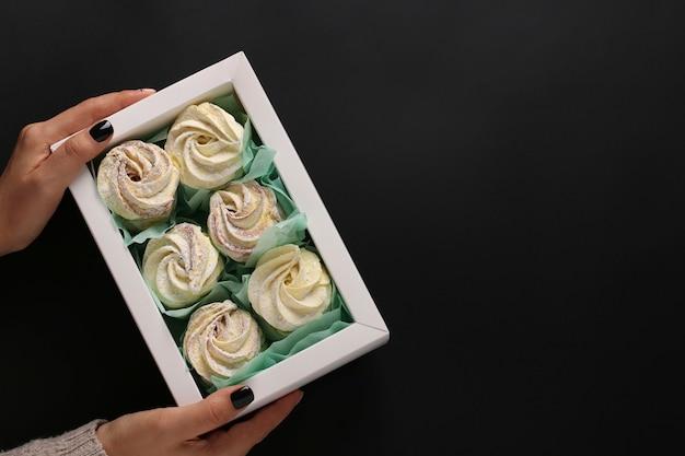 Caixa com marshmallows caseiros em mãos femininas em um fundo escuro, orientação horizontal, vista superior, espaço de cópia