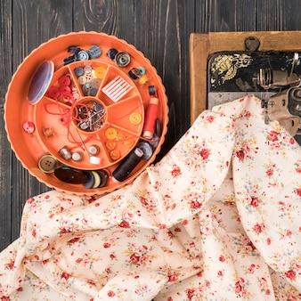 Caixa com material de costura na mesa de madeira