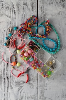 Caixa com miçangas, alicate e corações de vidro para criar jóias feitas à mão em madeira velha