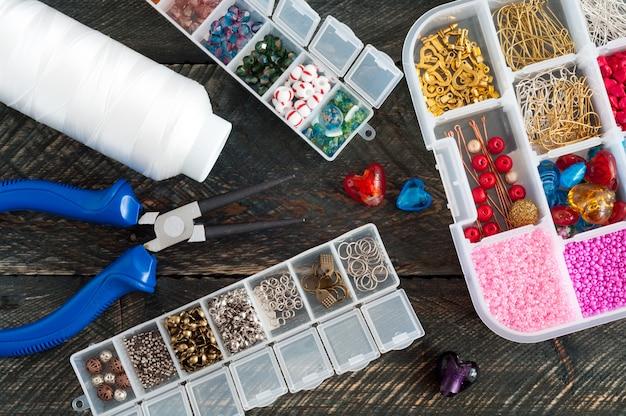 Caixa com miçangas, carretel de linha, alicate e corações de vidro para criar jóias feitas à mão sobre fundo de madeira velho. acessórios artesanais