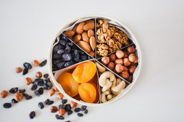 Caixa com nozes e frutas secas, lanche saudável, nutrição adequada