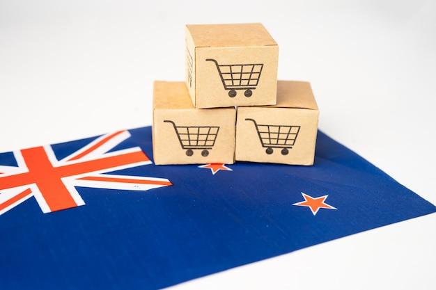 Caixa com o logotipo do carrinho de compras e a bandeira da nova zelândia, importação, exportação, compras on-line ou entrega de produtos da loja de serviços de entrega de finanças de comércio eletrônico, comércio, conceito de fornecedor.