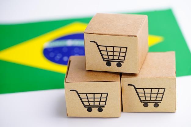 Caixa com o logotipo do carrinho de compras e a bandeira do brasil: importação exportação compras on-line ou entrega de produtos de loja de serviço de comércio eletrônico de envio, comércio, conceito de fornecedor.