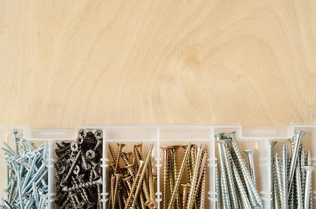 Caixa com parafusos de diferentes tamanhos em madeira clara