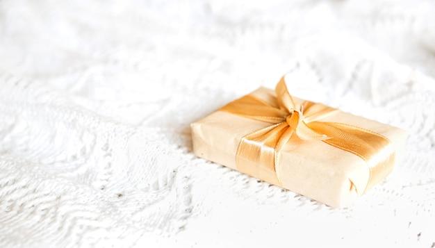 Caixa com presente de natal em papel leve amarrada com fita dourada