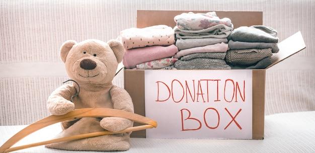 Caixa com roupas para caridade e ursinho com cabide