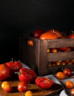 Caixa com tomates de outono e tábua de cortar