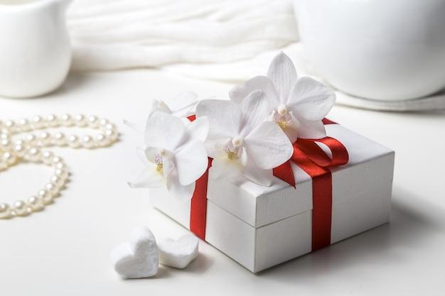Caixa com um presente e uma orquídea branca em um fundo branco.
