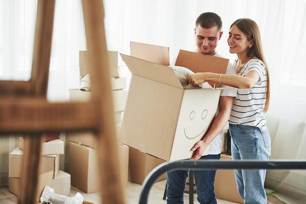 Caixa com um sorriso pintado. casal jovem alegre em seu novo apartamento. concepção de movimento.