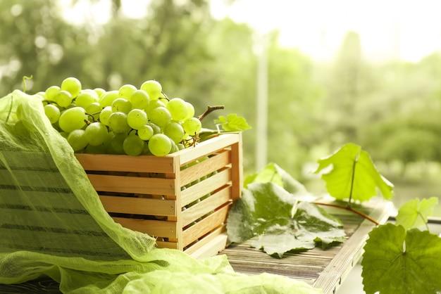 Caixa com uvas doces na mesa de madeira ao ar livre