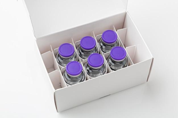Caixa com vacinas covid19 em fundo branco, prontas para vacinação.
