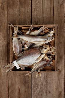 Caixa com vários peixes secos ao sol sobre fundo de pranchas de madeira