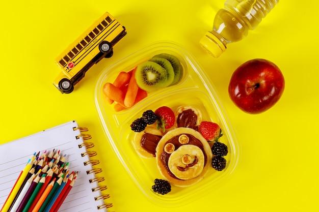 Caixa de almoço de crianças com panqueca, frutas e maçã na superfície amarela