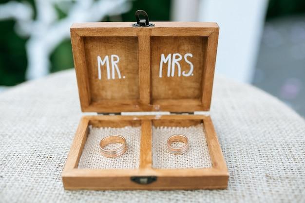 Caixa de anel de madeira com alianças de ouro