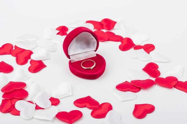 Caixa de anel em forma de coração de veludo vermelho com anel de noivado dentro entre corações de tecido vermelho e branco. presente para dia dos namorados, aniversário. conceito de proposta de casamento. fechar-se