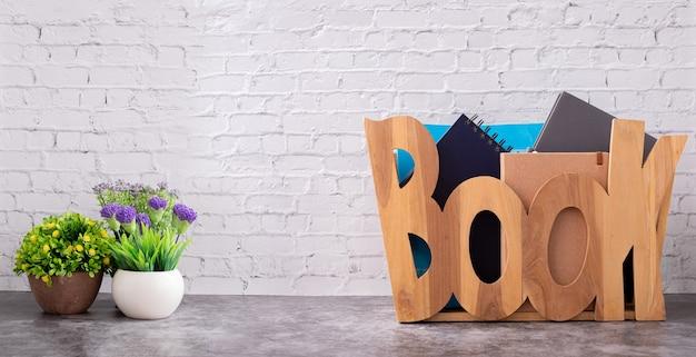 Caixa de armazenamento de caixa de madeira com vaso de flores na textura da parede de tijolo branco.