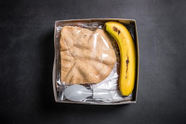 Caixa de arroz contendo arroz satay curry, banana de cabra e biscoitos pacotes aqiqah na indonésia
