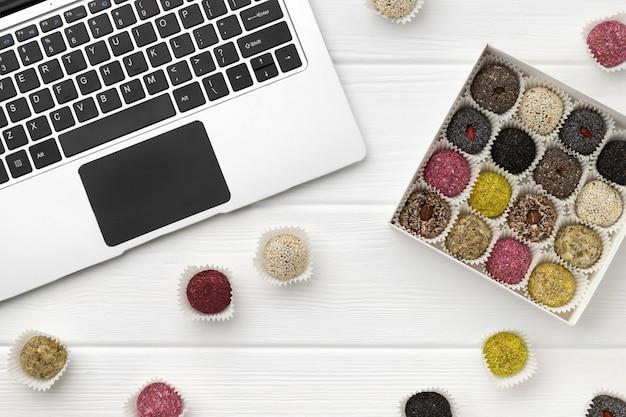 Caixa de bolas de energia vegan doces perto do laptop na mesa de madeira branca
