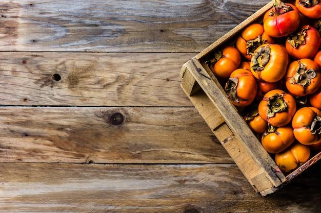 Caixa de caqui de caqui de frutas frescas em fundo de madeira