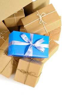 Caixa de cartão com vários pacotes de papel pardo e um único presente azul