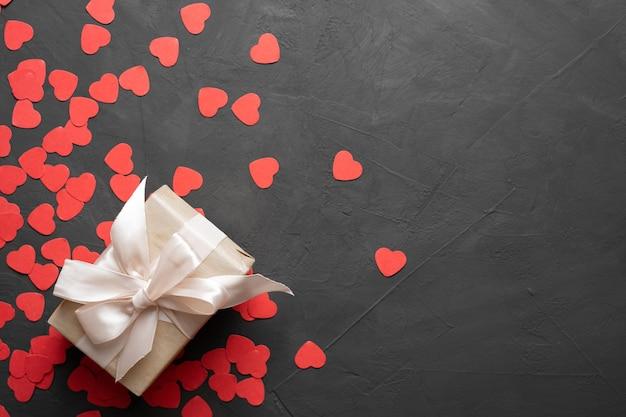 Caixa de cartão de dia dos namorados com caixa embalada e grande arco em fundo de pedra. copie a vista superior do espaço. postura plana