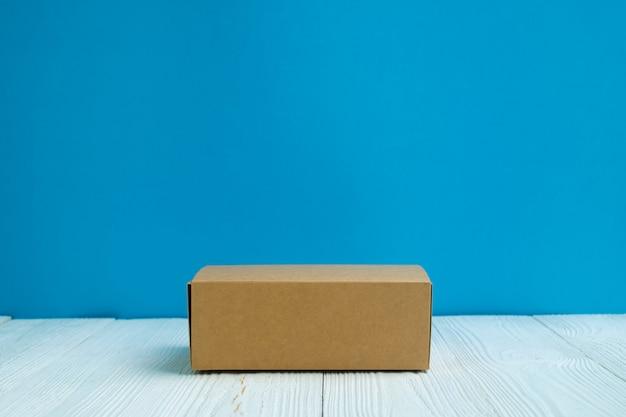 Caixa de cartão ou bandeja vazia do marrom do pacote na tabela de madeira branca brilhante com fundo azul da parede.