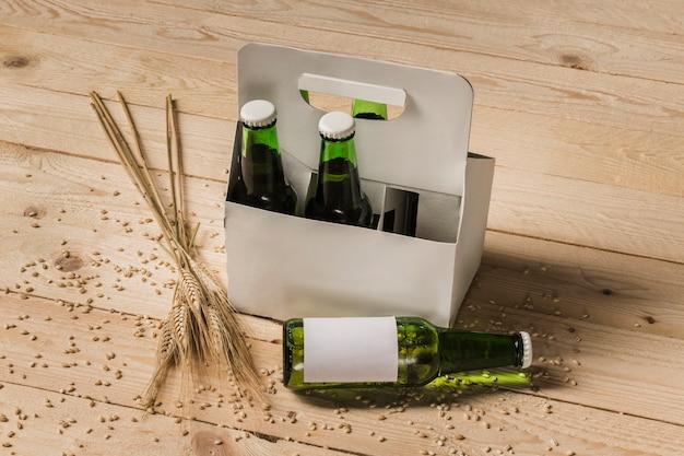 Caixa de cerveja e espigas de trigo no fundo de madeira