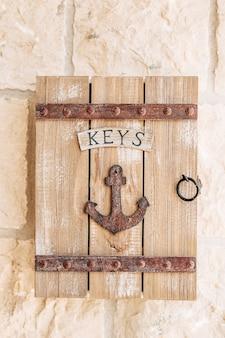 Caixa de chaves de madeira com inscrição e uma âncora de metal pendurada em uma parede de pedra