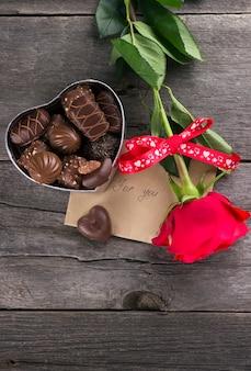 Caixa de chocolates, rosa vermelha em um fundo escuro