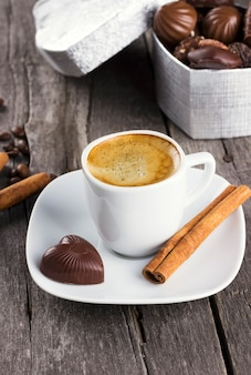 Caixa de chocolates, xícara de café em um fundo de madeira