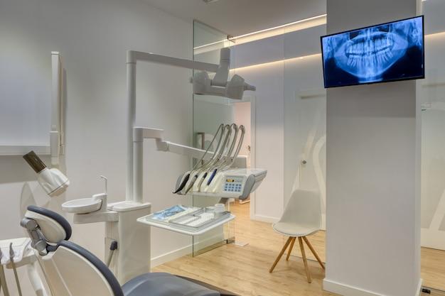 Caixa de clínica odontológica moderna e totalmente equipada, com paredes brancas, piso de madeira e raios-x, mostrados na tela da tv