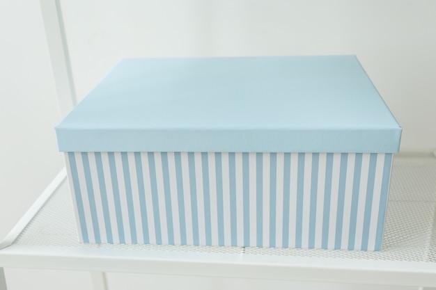 Caixa de compras de presente azul parada na prateleira dia de aniversário e conceito presente