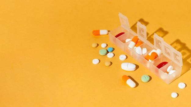 Caixa de comprimidos em fundo amarelo