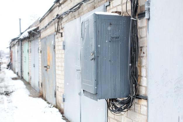 Caixa de comunicação elétrica velha pendurada na parede de uma cooperativa de garagem